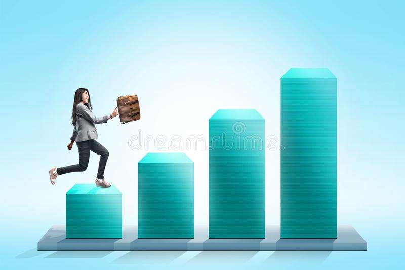 Attractive asian businesswoman with briefcase walking on the 3D chart stock illustration