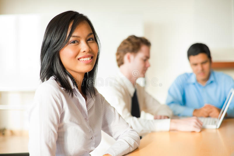 Attractive Asian Businesswoman Meeting. An attractive Asian businesswoman looks at the camera during a meeting with a diverse group of business people including stock photography