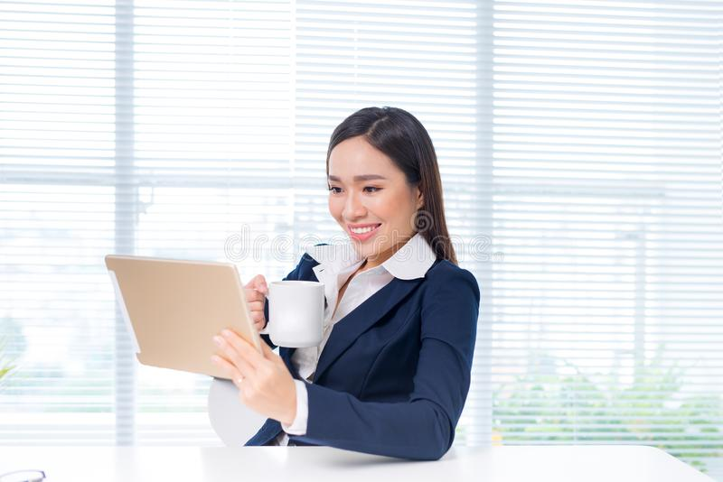 Attractive asian businesswoman working on a digital tablet in th royalty free stock photos