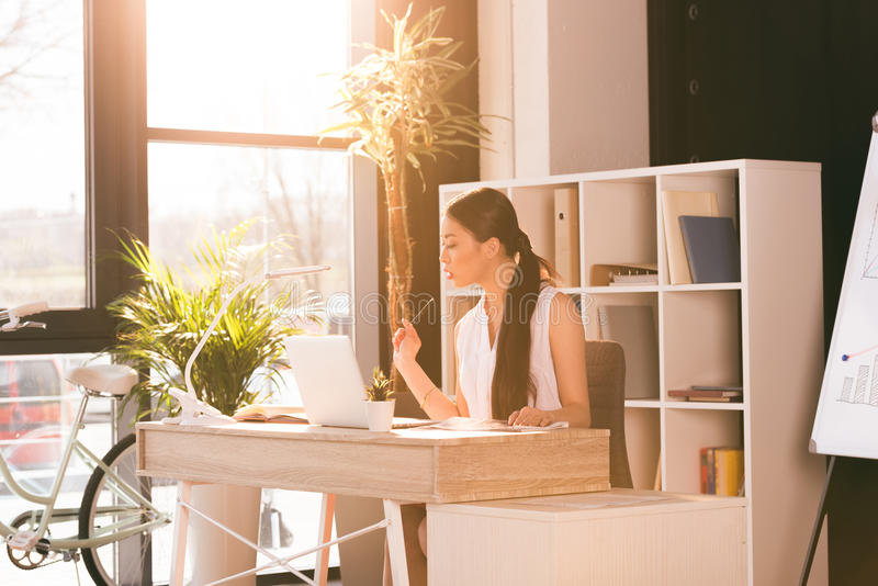 Attractive asian businesswoman working with laptop at workplace in office royalty free stock images