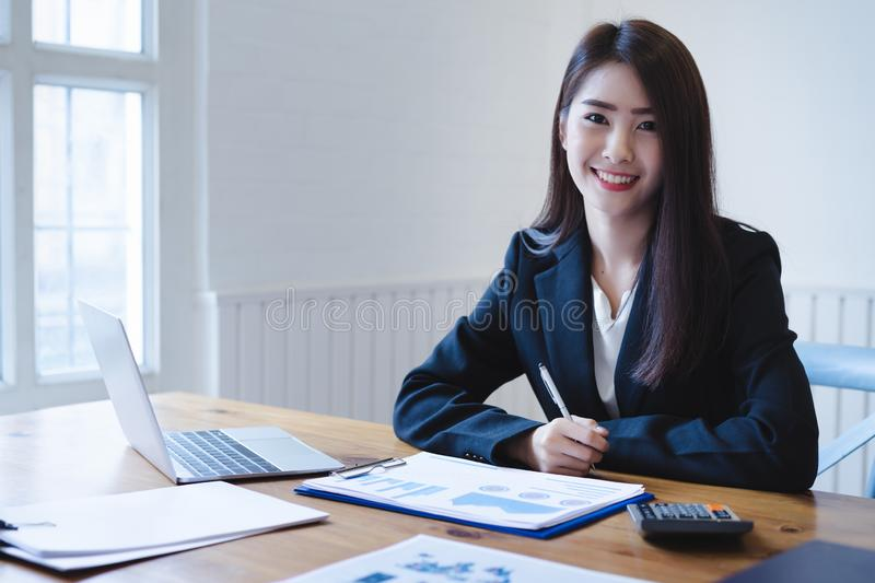 Attractive asian female accountant using calculator and discussing financial reports.finance accounting concept royalty free stock photo