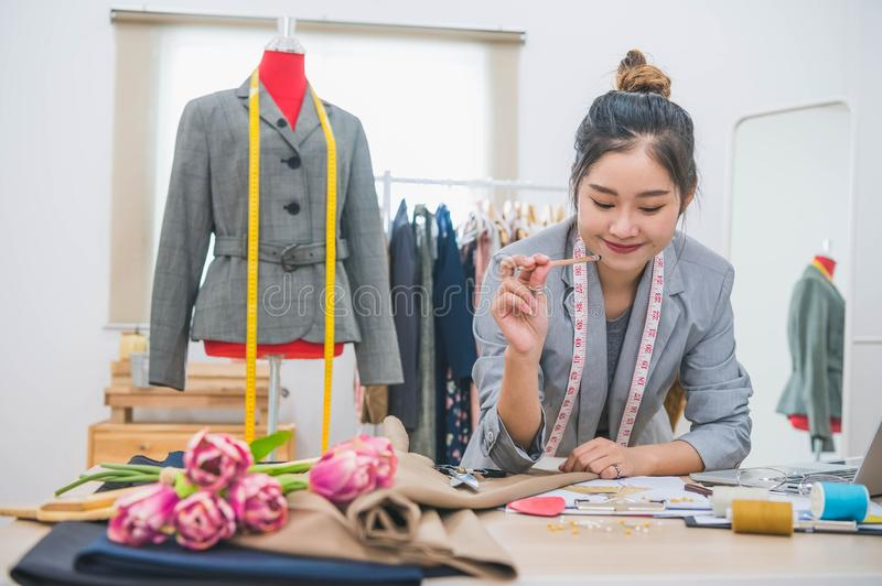 Attractive Asian female fashion designer  working in home office workshop. Stylish fashionista woman creating new cloth design royalty free stock photos