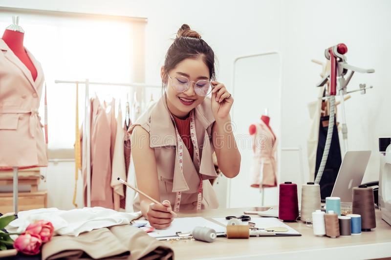 Attractive Asian female fashion designer working in home office workshop. Stylish fashionista woman creating new cloth design stock image