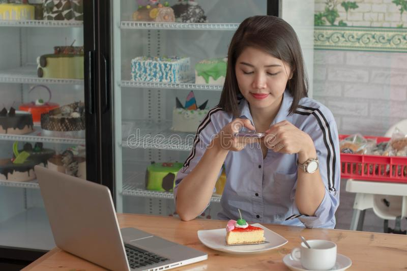 Attractive asian female taking picture slice of strawberry cake with smartphone to uploading on social media stock photos