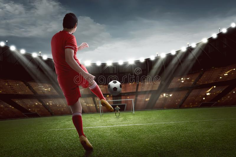 Attractive asian football player shooting the ball to goal royalty free stock photography