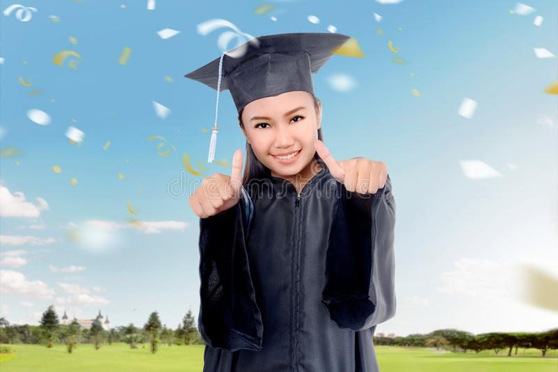 Attractive asian girl celebrate graduation with graduation gown. And hat on the campus royalty free stock photography