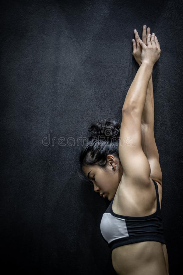 Attractive Asian girl stretching arm on black wall stock image