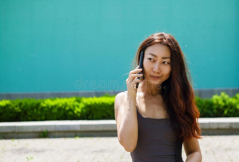Happy asian girl talking over mobile phone while waking in the street. Attractive asian girl talking over mobile phone while waking in the street. Cheerful royalty free stock image