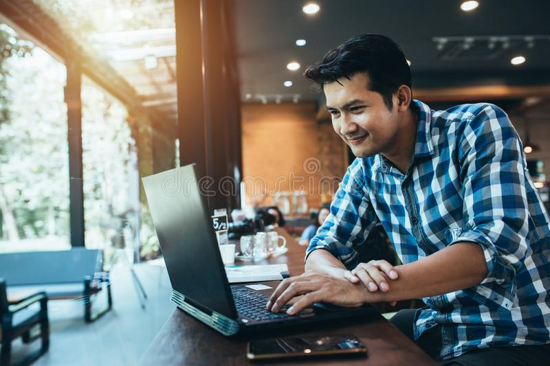 Attractive asian male is typing messages on a laptop while sitting against the wide windows of a coffee shop. a hipster girl is stock images