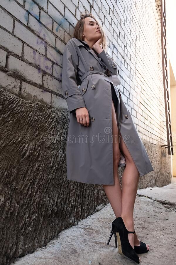 Free Attractive Asian Model In Trench Coat Standing Near Wall Shot From Lower Point Royalty Free Stock Photos - 197233768