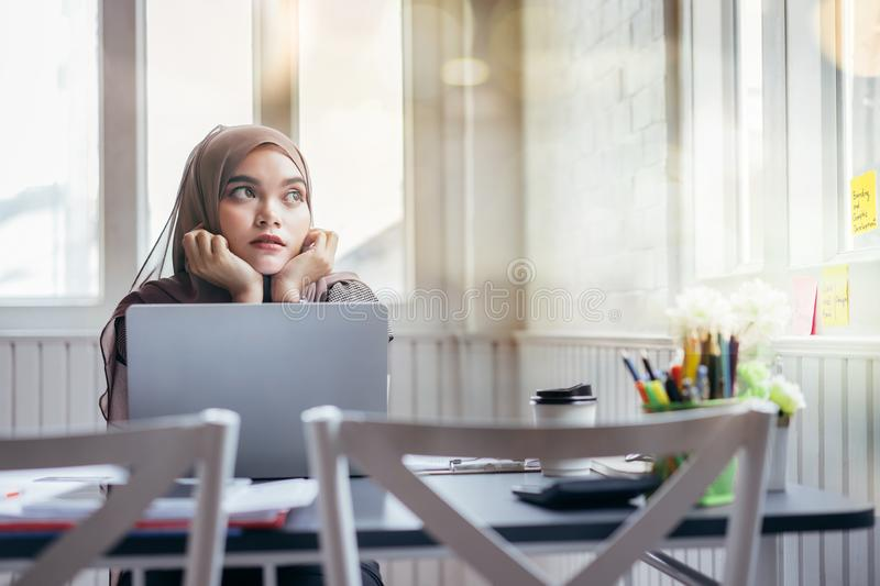 Attractive asian muslim business woman brown hijab working at home looking outside royalty free stock images