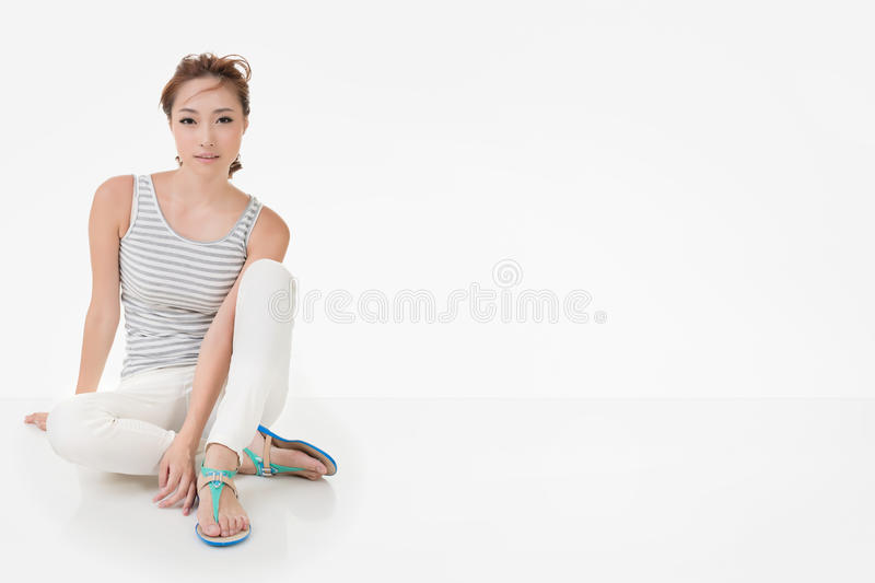 Attractive asian woman sit on ground. And looking to the camera. Full length portrait isolated on the white background stock image