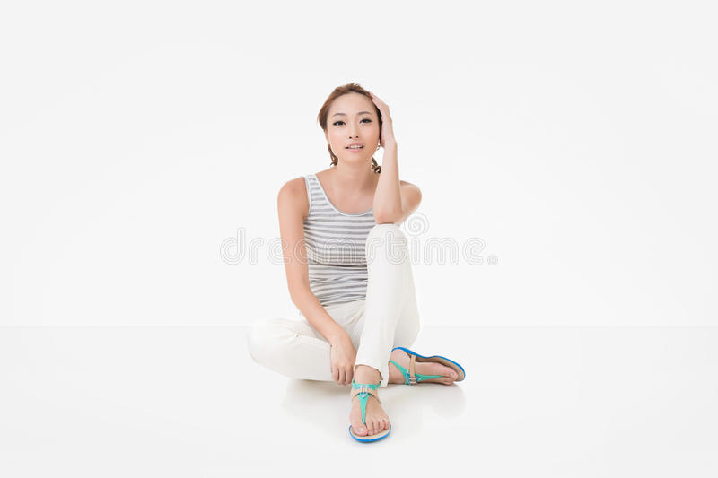 Attractive asian woman sit on ground. And looking to the camera. Full length portrait isolated on the white background stock images
