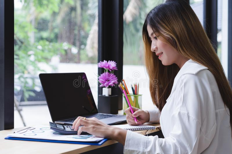 Attractive asian woman working about financial with laptop and calculator in co-working or coffee shop. Financial and accounting c royalty free stock image