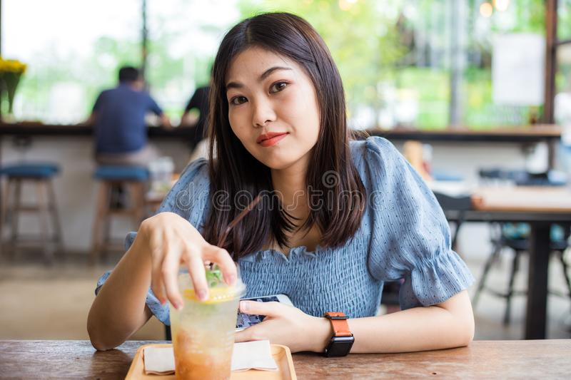 Attractive asian women sitting on wood table in cafe stock photo