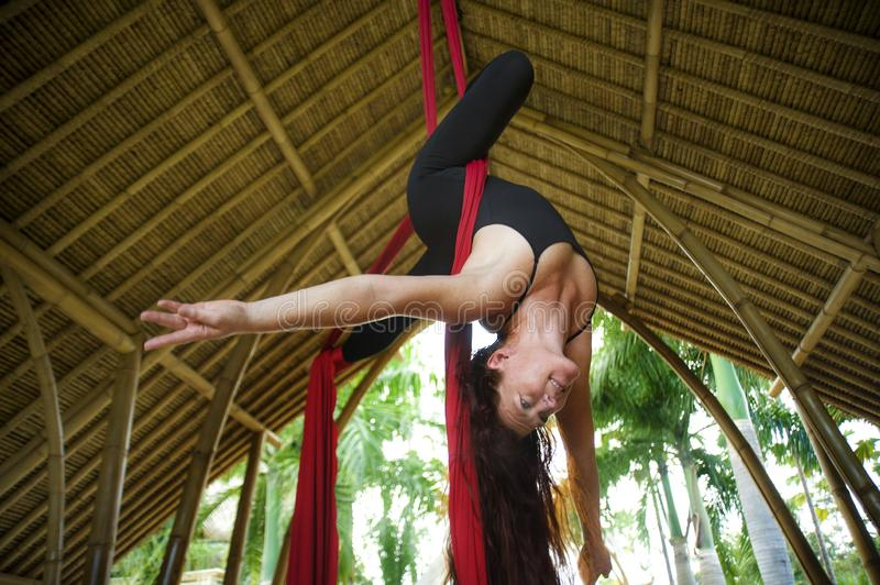 Attractive and athletic aerialist woman hanging from silk fabric doing aerial dancing workout training happy at beautiful hut in royalty free stock photography