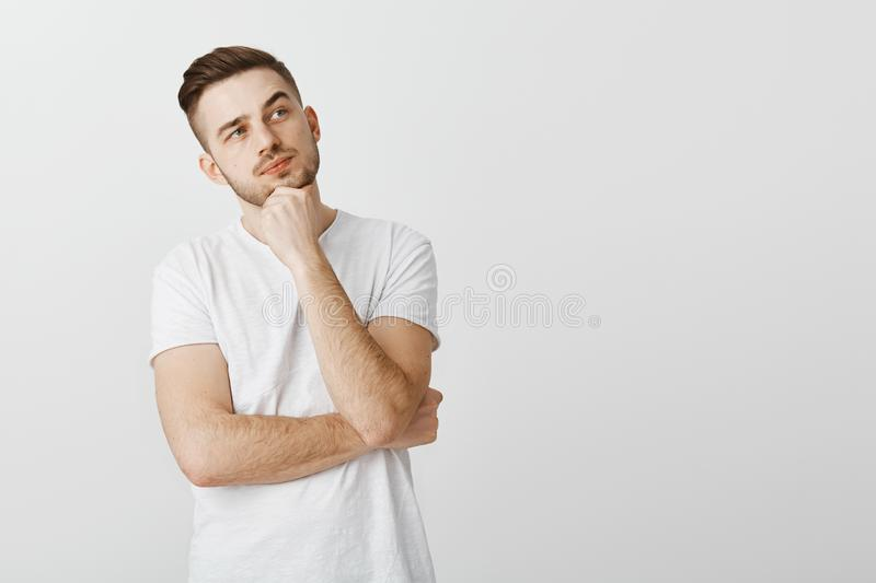 Attractive athletic european guy weighing opportunities and choies standing in thoughtful pose with fist on chin raising. Eyebrow looking at upper right corner stock photo