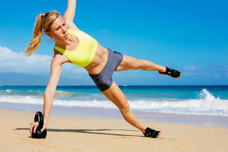 Attractive Athletic Woman Doing Kettle Bell Workout. Young attractive woman doing kettle bell exercises outside. Fitness woman working out at the beach. Crossfit royalty free stock photos