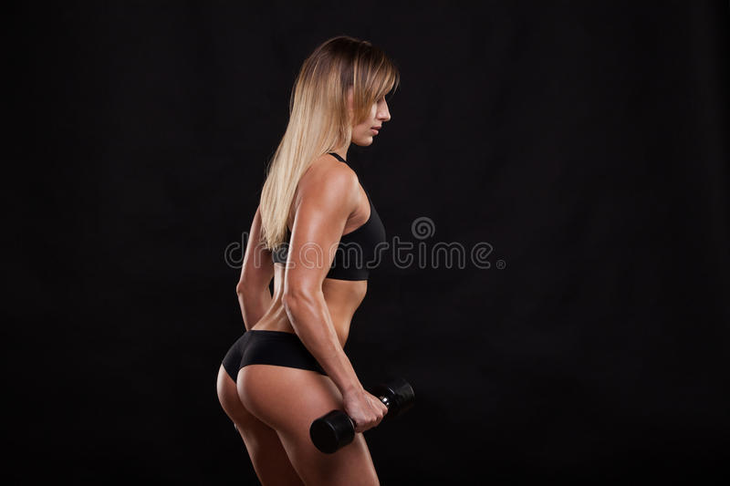 Attractive athletic woman is pumping up muscles with dumbbells, back view isolated on dark background with copyspace royalty free stock images