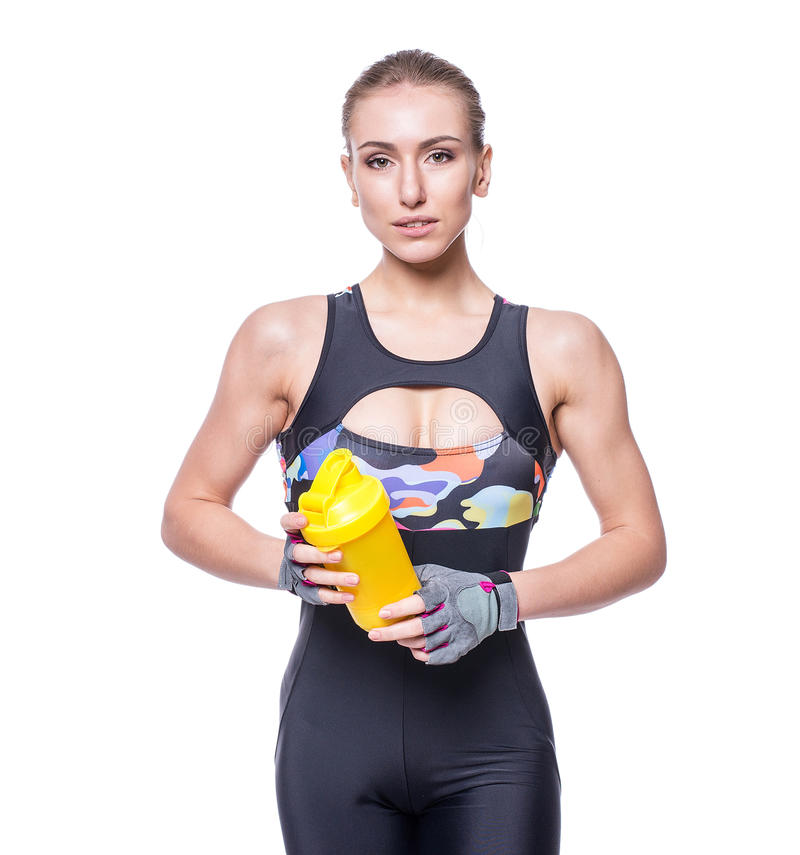 Attractive athletic woman relaxing after workout with shaker isolated over white background. Healthy girl drinks whey protein. Attractive athletic woman royalty free stock images