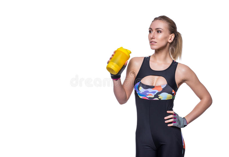 Attractive athletic woman relaxing after workout with shaker isolated over white background. Healthy girl drinks whey protein. Copyspace for text royalty free stock photography