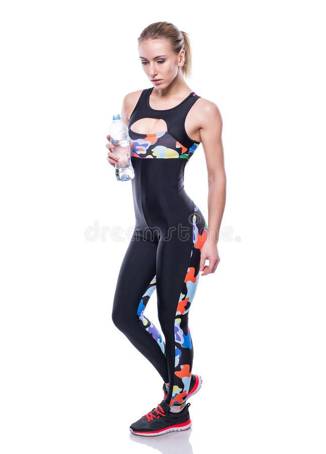Attractive athletic woman after workout with bottle of water isolated over white background. Healthy girl drinks pure water. royalty free stock photos