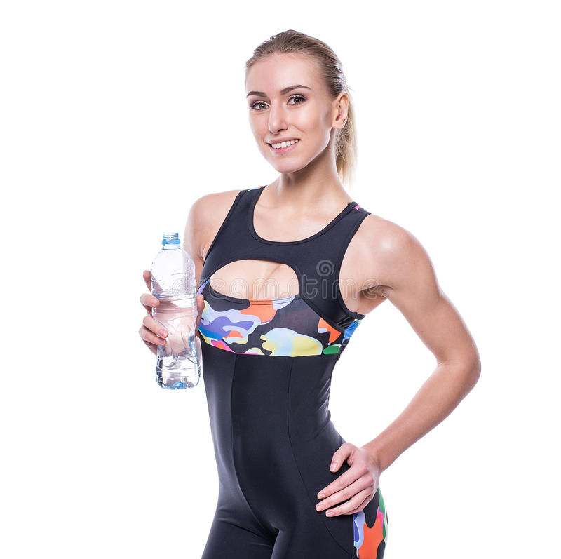 Attractive athletic woman after workout with bottle of water isolated over white background. Healthy girl drinks pure water. royalty free stock image