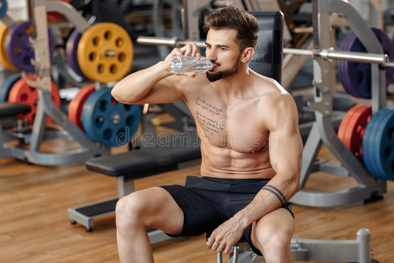 Attractive athletic young man bodybuilder fitness model drink water after exercise with barbell on the bench in gym. Attractive athletic young man bodybuilder stock photo