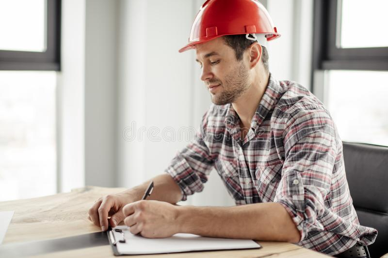 Attractive awesome constructor is writing down the costs for reconstruction. Close up side view photo stock images