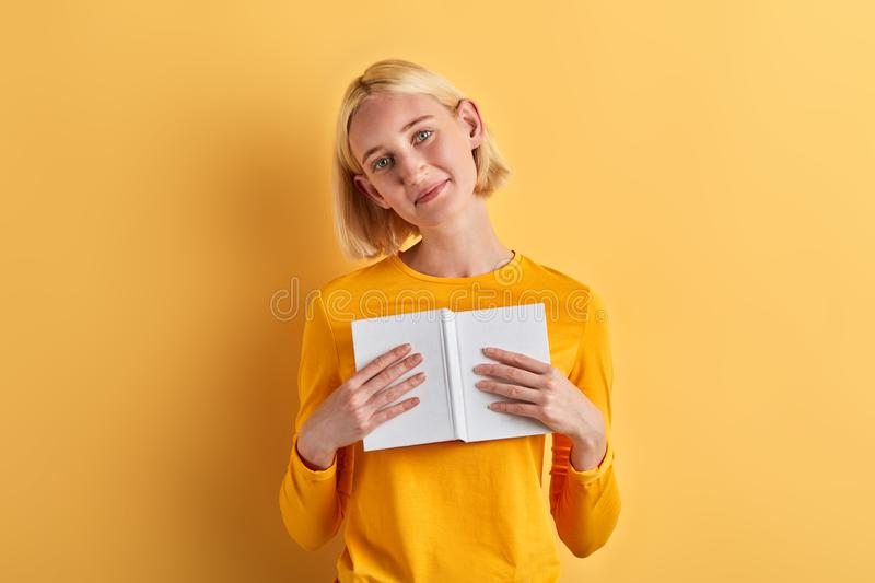 Attractive awesome girl holding notebook and looking at the camera royalty free stock photography