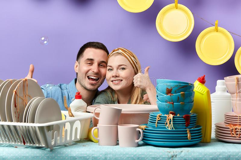 Attractive awesome young couple showing thumbs up while looking at the camera royalty free stock image
