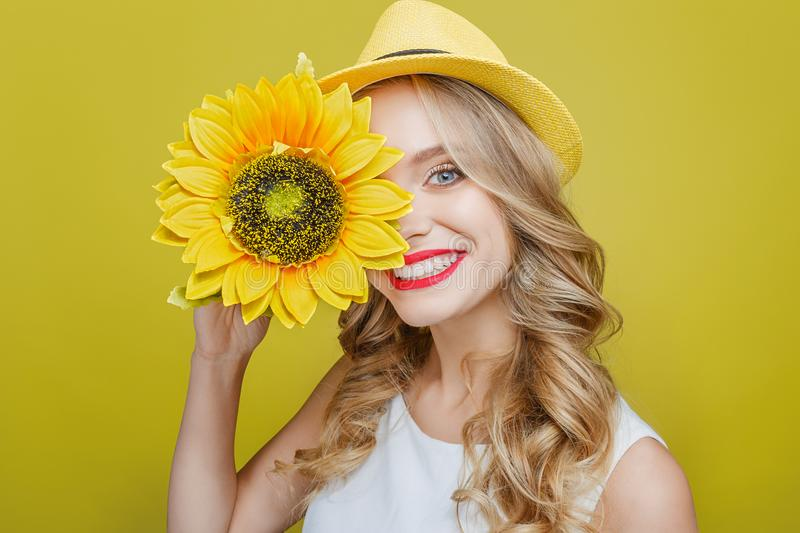 Attractive and awesome young woman is holding a sun flower close to her face. She is looking to camera and smiling. This. Person is very cheerful. Isolated on stock image