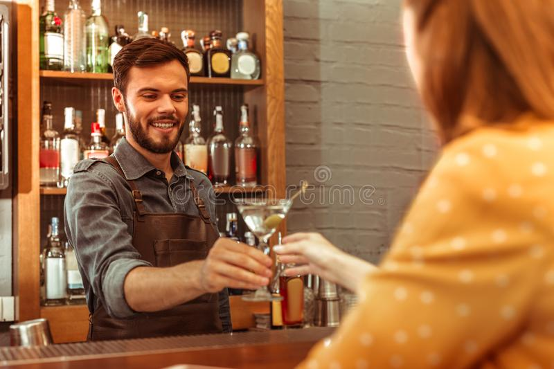 Attractive bartender giving a martini cocktail to a woman. Giving a martini cocktail. Attractive beaming good-looking dark-haired adult bartender wearing dark royalty free stock photos