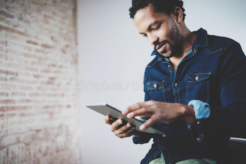 Attractive bearded African man using tablet at his modern home office.Concept of young people working mobile devices. Blurred background stock images
