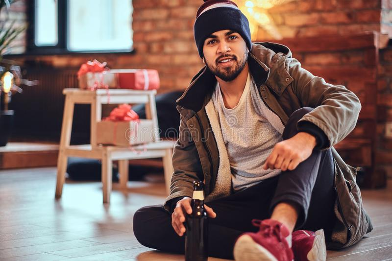 A man drinks beer. Attractive bearded Indian male drinks craft beer in a room with Christmas decoration royalty free stock photos