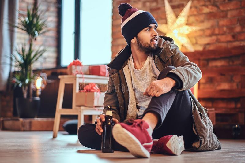 A man drinks beer. Attractive bearded Indian male drinks craft beer in a room with Christmas decoration royalty free stock image