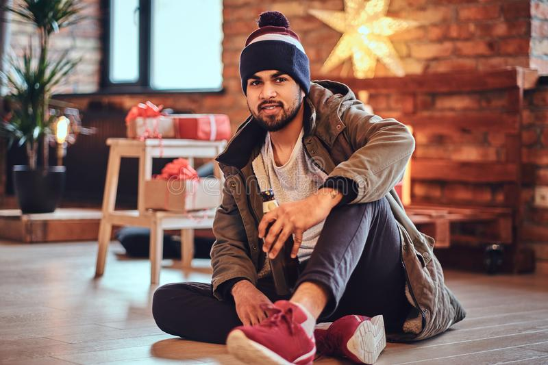 A man drinks beer. Attractive bearded Indian male drinks craft beer in a room with Christmas decoration royalty free stock photography