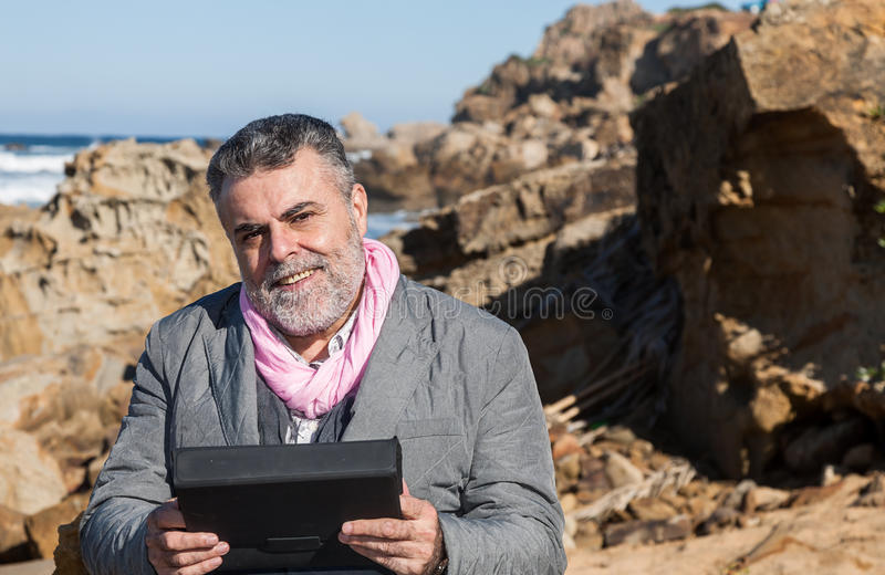Attractive bearded man on the beach. With tablet royalty free stock image