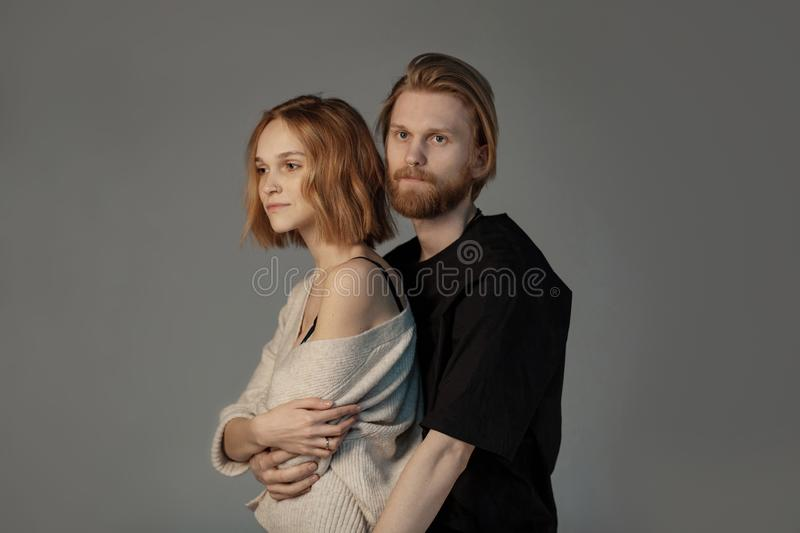 Attractive bearded man with long brown hair hugging her beautiful young girlfriend stock image