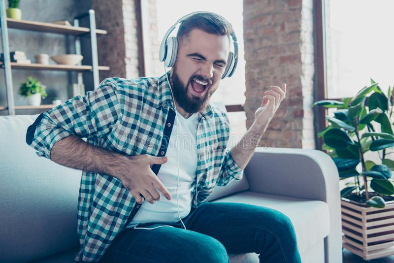 Attractive, bearded man sitting on the couch in living room, having headphones on his head, listening his favorite music, singing royalty free stock images