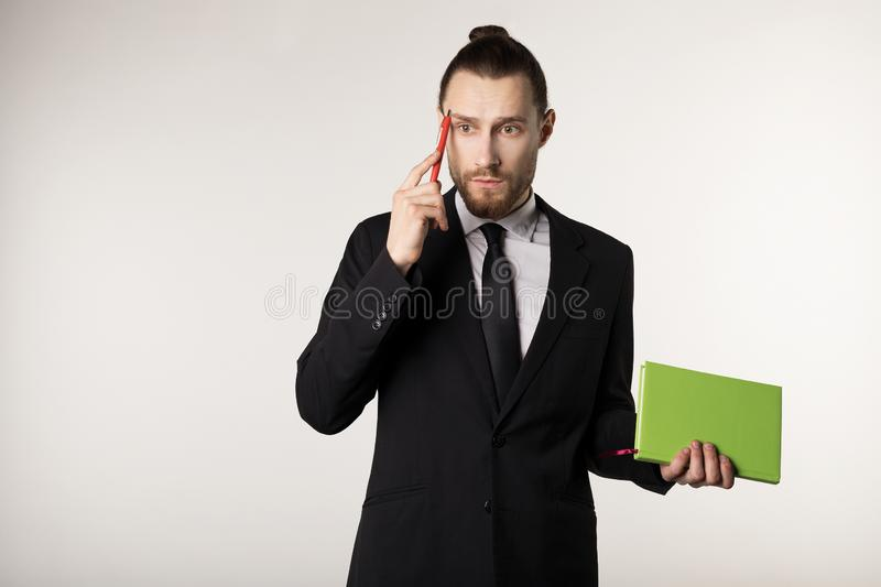 Attractive bearded middle manager is thinking how to solve the problem posed by the boss. Over white background stock image
