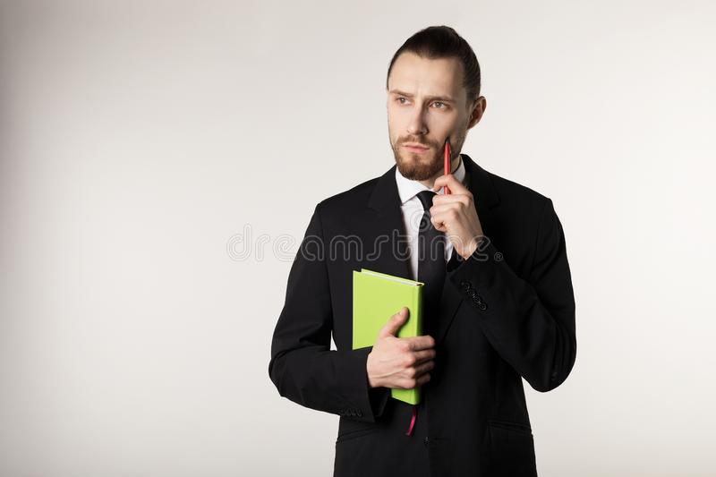 Attractive bearded middle manager is thinking how to solve the problem posed by the boss. Over white background stock photo