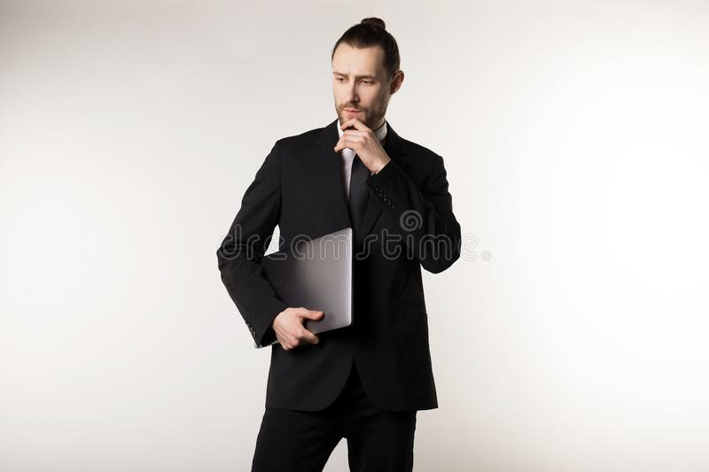 Attractive bearded middle manager wearing black suit and tie thinking with laptop in hands how to solve the problem stock photography