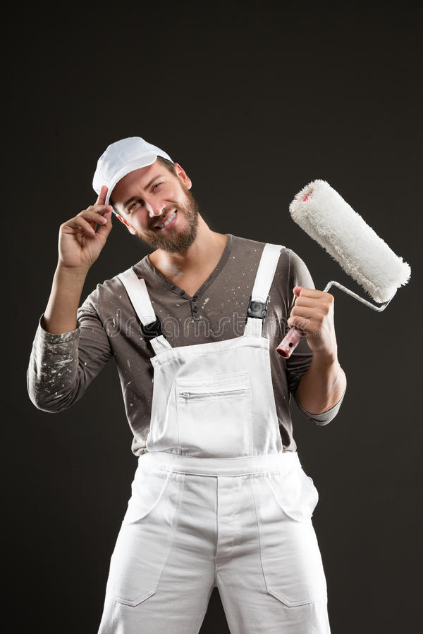 Attractive bearded young painter with paint roller stock photo