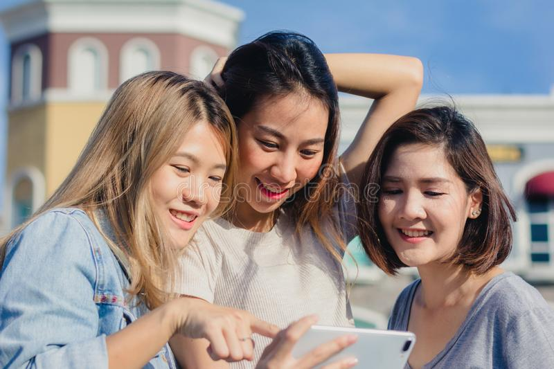 Attractive beautiful asian friends women using a smartphone. Happy young asian teenage at urban city while taking self portraits. stock photos