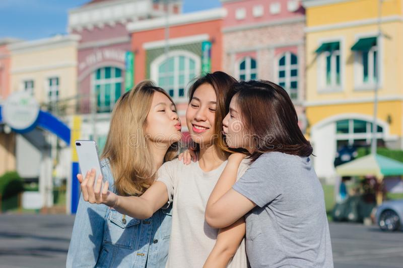 Attractive beautiful asian friends women using a smartphone. Happy young asian teenage at urban city while taking self portraits. royalty free stock photos