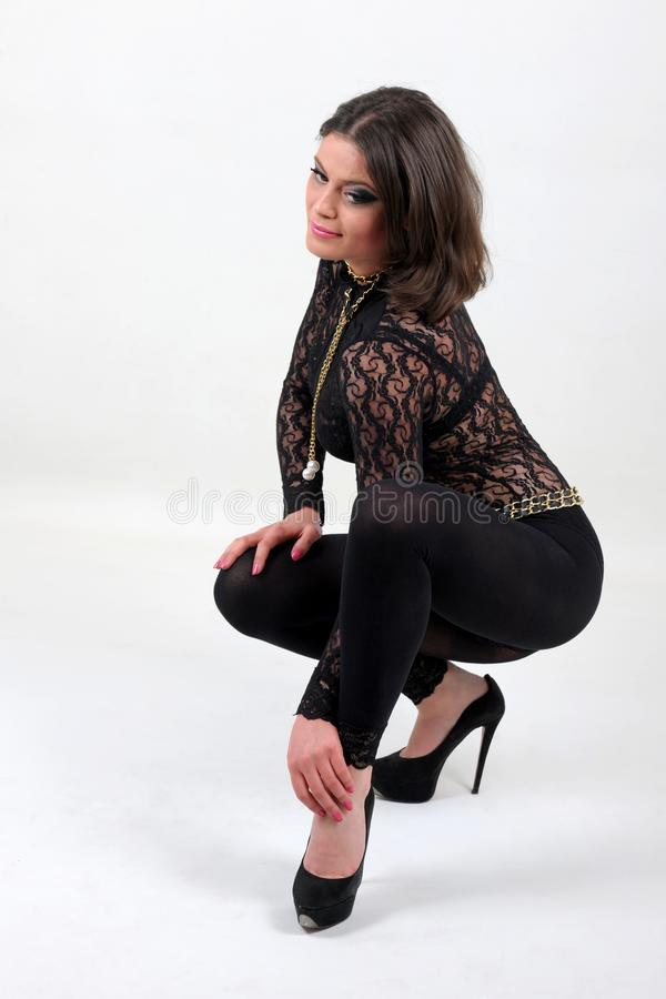 Attractive, beautiful and beautiful girl kneel and poses in a studio stock photography