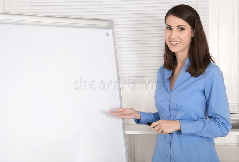 Attractive beautiful business woman before a flip chart. royalty free stock photos