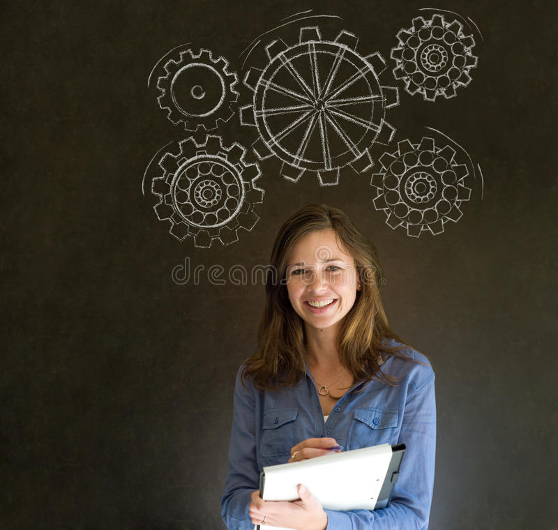 Woman thinking with turning gear cogs or gears. Attractive beautiful business woman, student or teacher thinking with turning gear cogs or gears royalty free stock image
