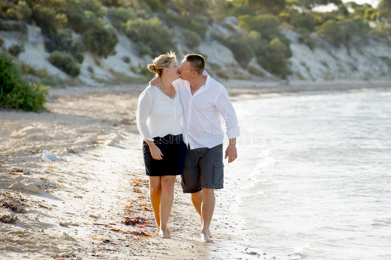 Attractive beautiful couple in love walking on the beach kissing in romantic summer holidays. Young attractive and beautiful American couple in love walking on royalty free stock images
